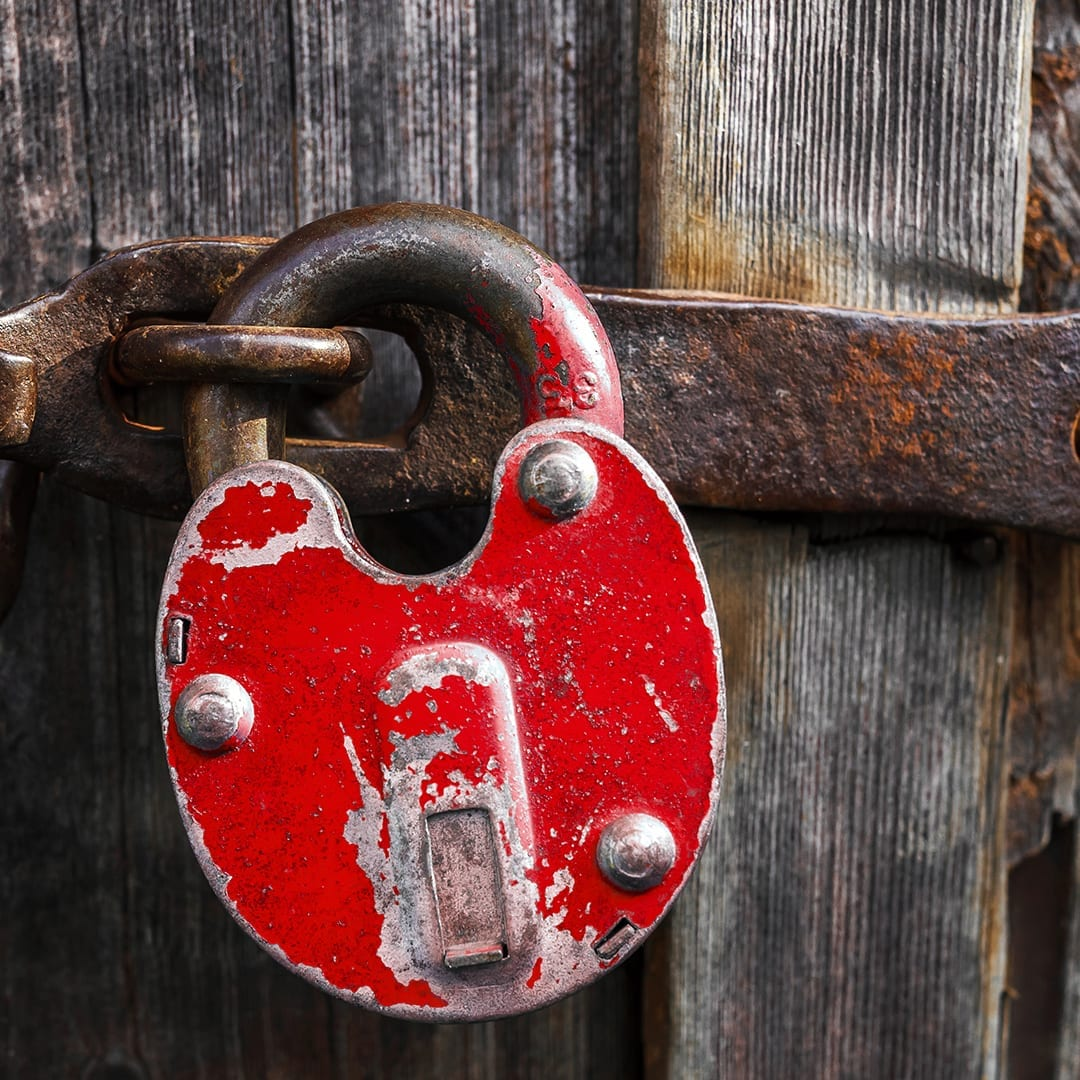 photo of a distressed red padlock on a rustic barn, representing country decor